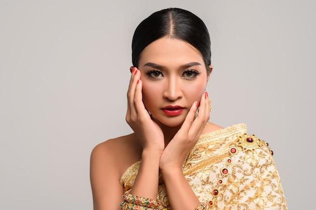 Женщина носит тайское платье, а руки касаются лица.