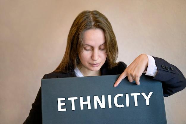 女性白人女性が立って、黒板の碑文ethnicityに指を向ける