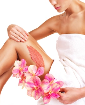 흰색에 그녀의 다리에 스크럽을 사용하여 꽃과 아름다운 몸매를 가진 여자