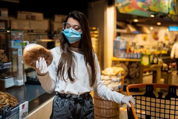 Женщина в хирургической маске собирается купить хлеб