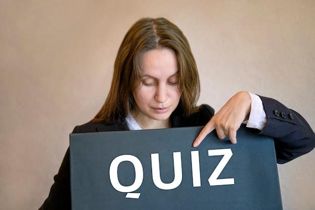 Женщина встает и указывает пальцем на надпись quiz на черной доске.