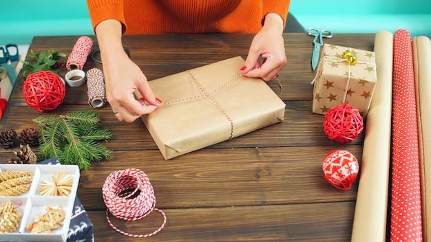 여자는 크리스마스를 위해 준비 선물을 포장합니다. 여자의 손과 선물의 클로즈업
