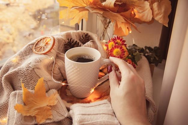 女性の手は彼女のコーヒーマグに手を伸ばします。セーターと秋の装飾に囲まれています
