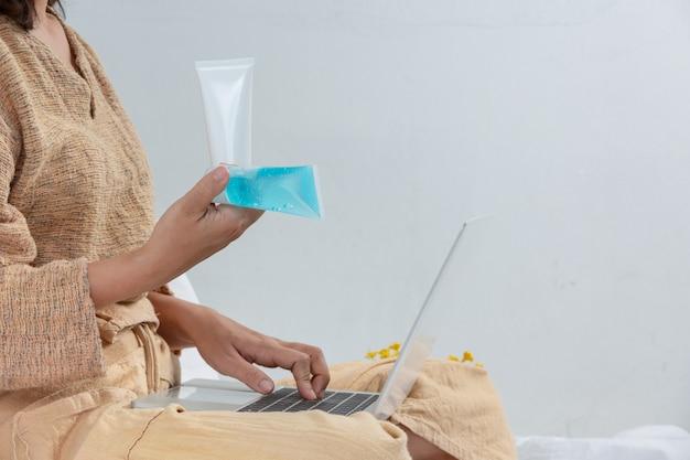 여자는 거실에서 일하는 동안 손 젤로 씻고있다.