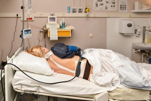 女性は、収縮と硬膜外麻酔で発祥の地に横たわっています