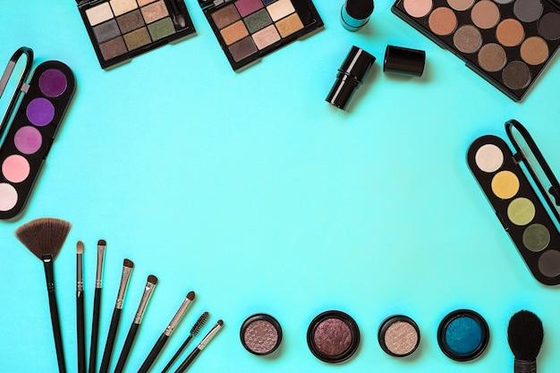 현대 여성의 파란색 배경에 여성용 화장품이 있습니다. 메이크업, 아이 섀도우, 위에서 볼 수 있는 브러시. 복사 공간