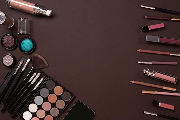 갈색 배경, 현대 여성의 여성용 화장품. 메이크업, 아이 섀도우, 위에서 볼 수 있는 브러시. 복사 공간