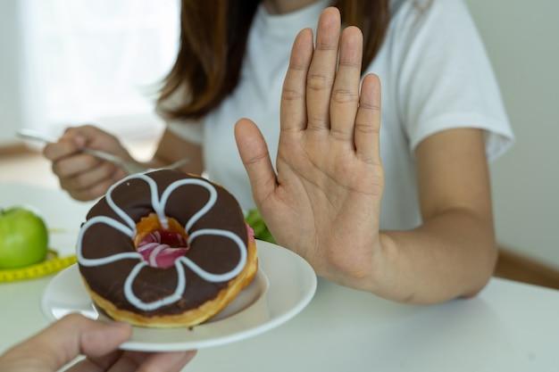 Женщины толкали тарелку с пончиками вместе с людьми. не ешьте десерты для похудения.