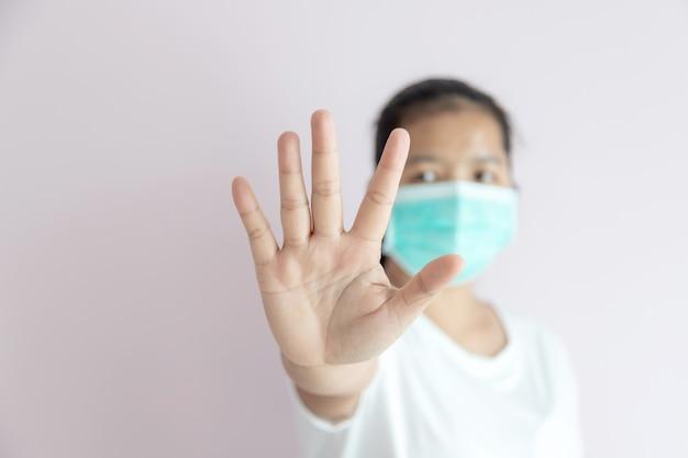 女性は保護のために医療用マスクを着用し、武漢コロナウイルスの発生を止めるために身振りで止めます