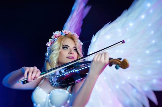 Женщины с крыльями ангела играют на скрипке в неоновом свете