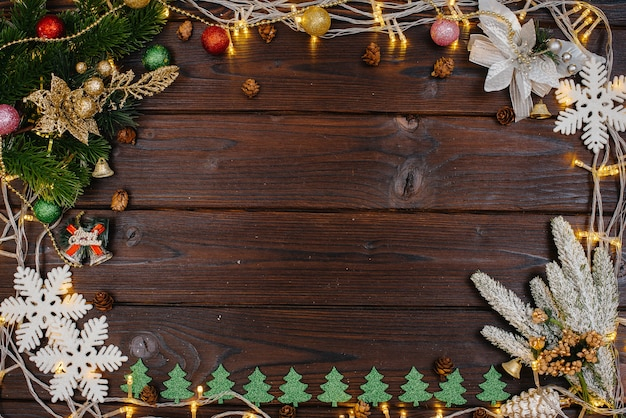 Деревянный новогодний фон украшен нарядным декором, фонариками, снежинками и ветками елки.