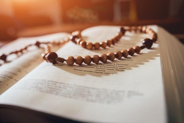 Деревянный крест над открытой библии на деревянный стол