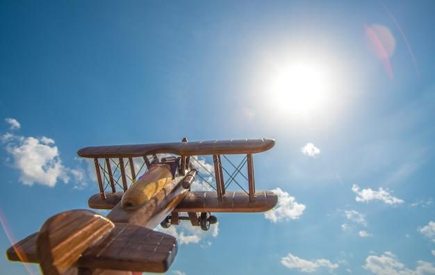 木製の飛行機は明るい太陽を背景に飛ぶ