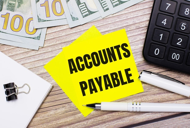 На деревянном столе есть калькулятор, банкноты, ручка, канцелярские скрепки и желтые наклейки с надписью «счета к оплате». бизнес-концепция