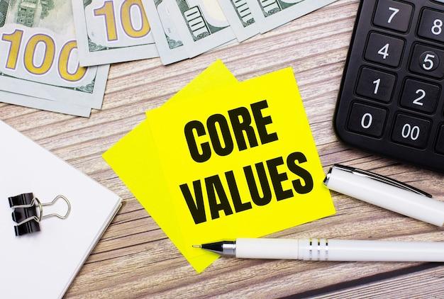 На деревянном столе есть калькулятор, банкноты, ручка, скрепки и желтые наклейки с текстом основные ценности. бизнес-концепция