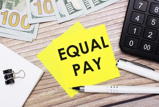 На деревянном столе есть калькулятор, банкноты, ручка, скрепки и желтые наклейки с надписью equal pay. бизнес-концепция