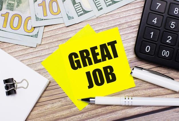 На деревянном столе есть калькулятор, банкноты, ручка, скрепки и желтые наклейки с надписью great job. бизнес-концепция