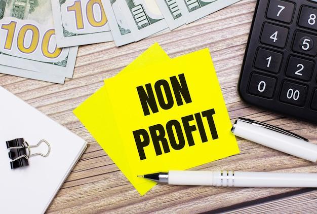 На деревянном столе есть калькулятор, банкноты, ручка, скрепки и желтые наклейки с надписью non profit. бизнес-концепция