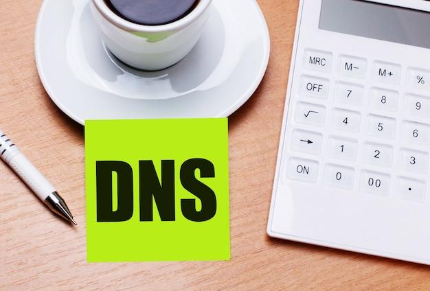 На деревянном столе есть белая чашка кофе, ручка, белый калькулятор и зеленая наклейка с текстом dns domain name system. бизнес-концепция
