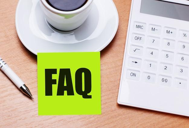 木製のテーブルには、白い一杯のコーヒー、ペン、白い電卓、そしてよくある質問のテキストが書かれた緑色のステッカーがあります。ビジネスコンセプト