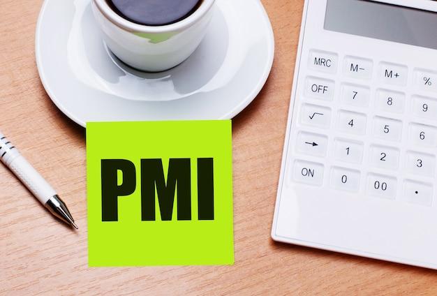 木製のテーブルには、白い一杯のコーヒー、ペン、白い電卓、そしてpmi project managementinstituteというテキストの付いた緑色のステッカーがあります。ビジネスコンセプト