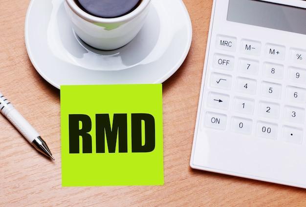 木製のテーブルには、白い一杯のコーヒー、ペン、白い電卓、および「rmd requiredminimumdistributions」というテキストが付いた緑色のステッカーがあります。ビジネスコンセプト