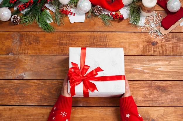 Деревянный стол с елочными украшениями и подарочной коробкой