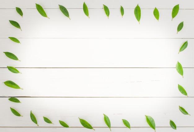 Деревянный стол с зелеными листьями вокруг рамки.