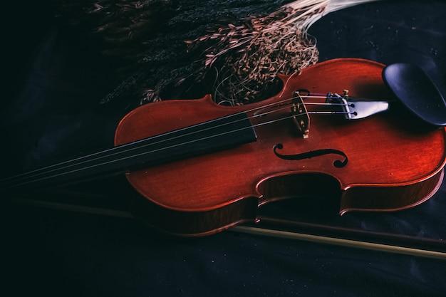 グランジ表面の背景、ヴィンテージ、アートトーンのドライフラワーの横に置く木製バイオリン