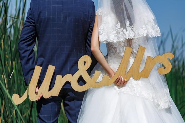 新婚夫婦の手の中にある「ミスターとミセス」の木の言葉。新郎新婦。幸せなちょうど結婚されていたカップル