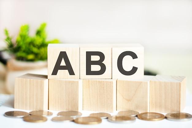 나무 큐브, 지폐 및 계산기 배경에 단어 abc.