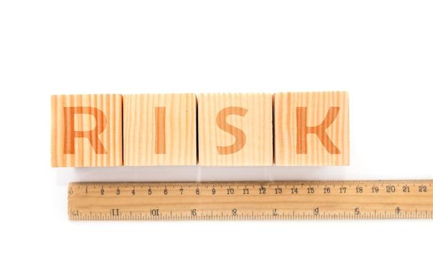 白い背景の定規の後ろにあるブロックのリスクについての言葉。