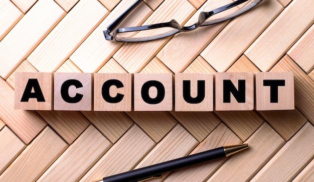 Слово аккаунт написано на деревянных кубиках на деревянном фоне рядом с ручкой и очками.