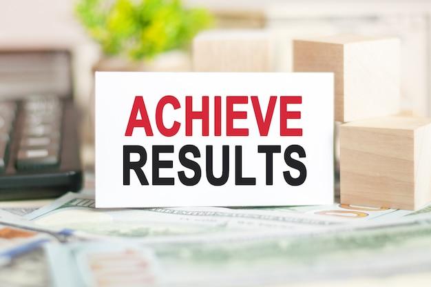 Achieve results라는 단어는 나무 큐브 근처의 백서 카드, 지폐 계산기에 기록됩니다.