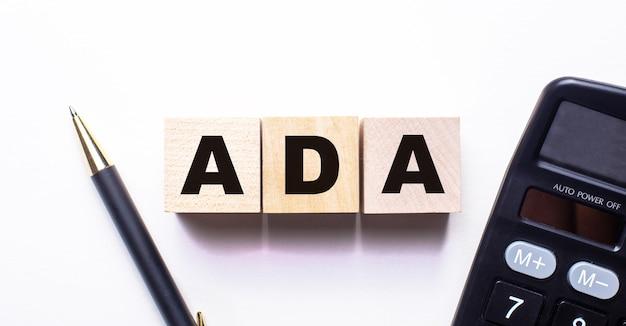 Слово ada написано на деревянных кубиках между ручкой и калькулятором на белом.