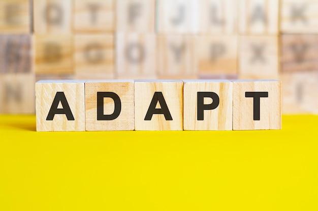 Слово адаптироваться написано на деревянных кубиках на ярко-желтой поверхности. на заднем плане ряды кубиков с разными буквами. концепция бизнеса и финансов