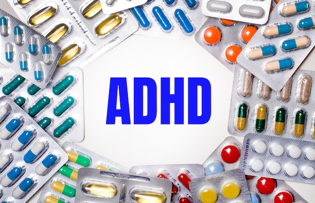 Слово adhd написано на светлом фоне в окружении разноцветных упаковок с таблетками. медицинская концепция