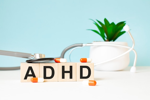 Adhdという言葉は、木製の背景にある聴診器の近くの木製の立方体に書かれています。医療コンセプト