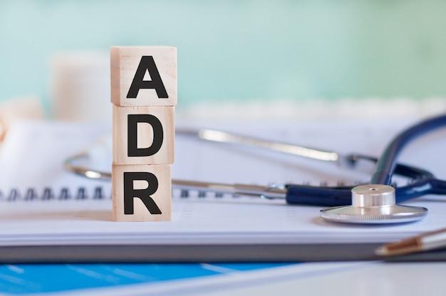 Слово adr написано на деревянных кубиках возле стетоскопа на поверхности бумаги.