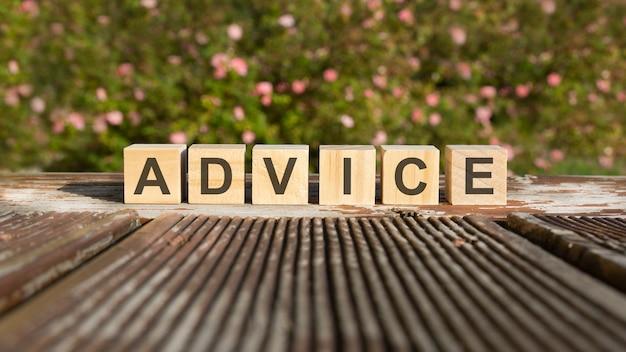Слово совет написано на деревянных кубиках. блоки кладут на старую деревянную доску, освещенную солнцем. на заднем плане - ярко цветущий куст