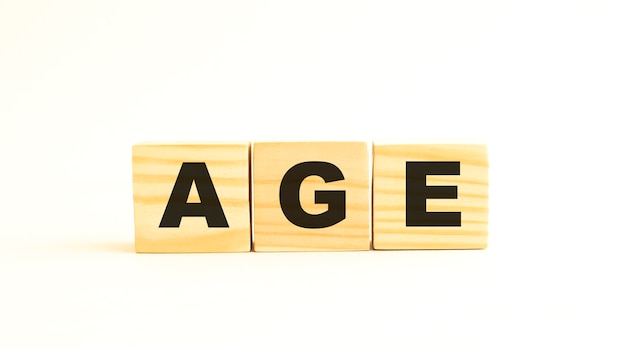 Age라는 단어. 흰색 배경에 고립 된 편지와 함께 나무 큐브. 개념적 이미지.