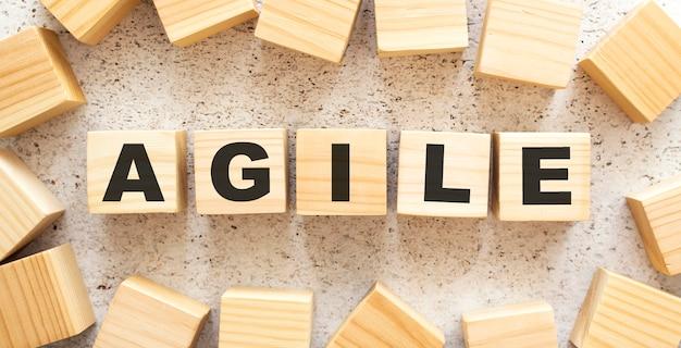 アジャイルという言葉は、明るい背景に上面図の文字が付いた木製の立方体で構成されています。作業スペース。