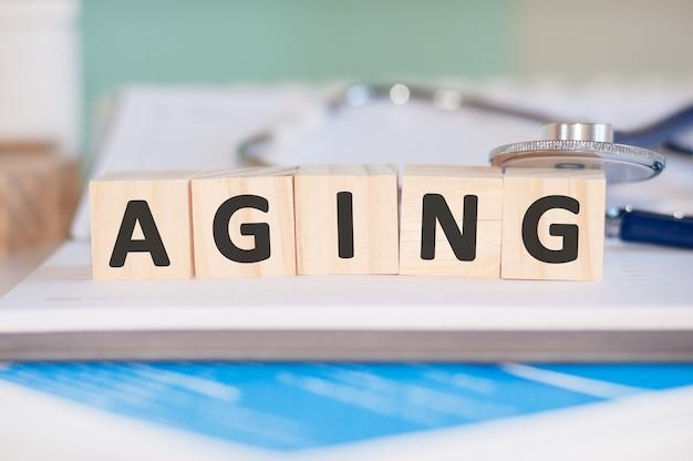 Слово старение написано на деревянных кубиках возле стетоскопа на бумаге. медицинская концепция.