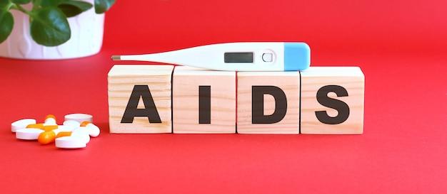 エイズという言葉は、医薬品が入った木製の立方体でできています。医療の概念。