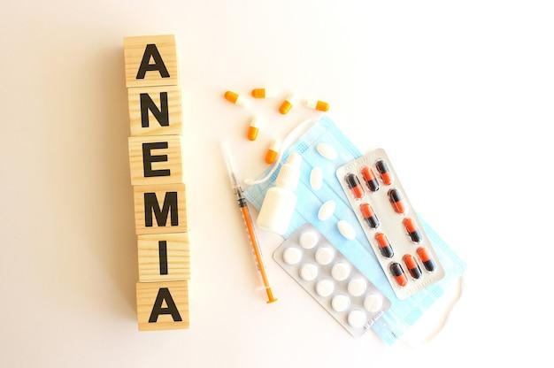 Слово анемия состоит из деревянных кубиков на белом фоне с медицинскими препаратами и медицинской маской.