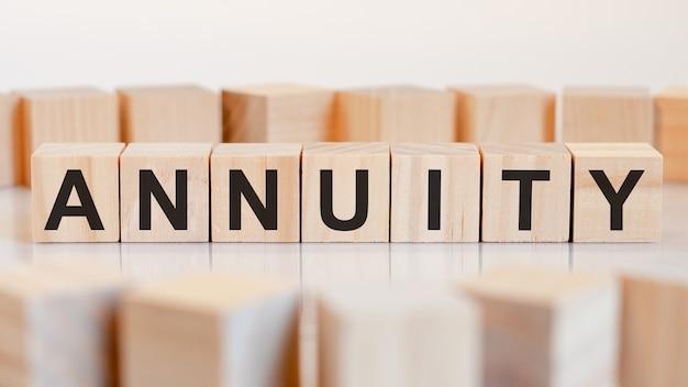 Annuityという言葉は木製の立方体の構造に書かれています。ビジネスと財務の概念。