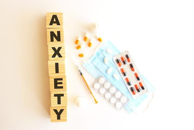 Anxiety라는 단어는 흰색 배경에 나무 큐브로 만들어졌습니다. 의료 개념입니다.