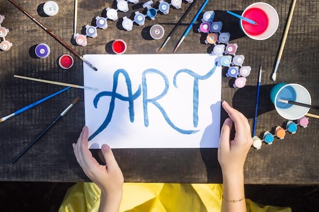 アートという言葉は、ブラシや絵を描くことの間で白い紙の上に青いペンキで書かれています。創造性と趣味のコンセプト
