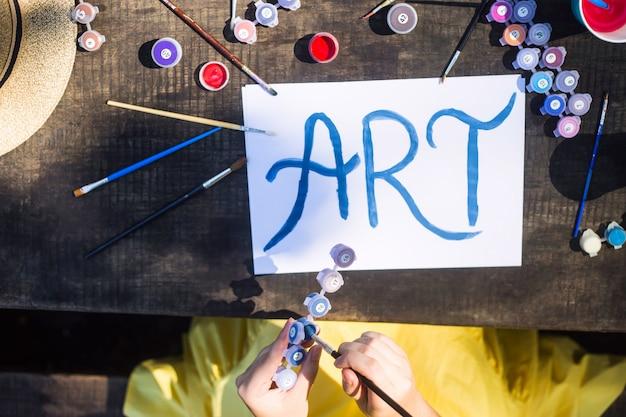 アートという言葉は、ブラシや絵を描くことの間で白い紙に青い絵の具で書かれています