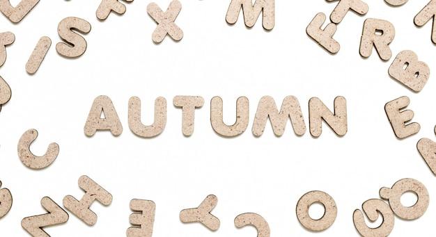 Слово осень среди деревянных букв на белом